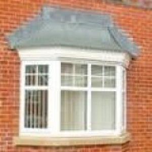Canopies above a bay window of a red brick house