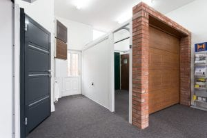 showroom with brown and white garage doors and grey security door